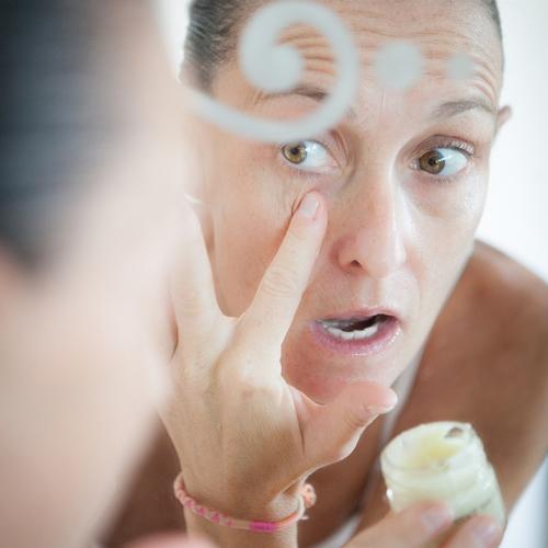 Visage de femme dans un miroir en train de mettre du beurre de karité sur sa peau